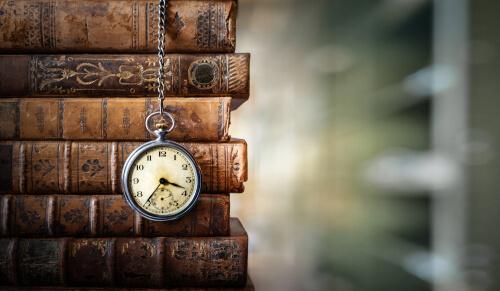 Livros e um relógio com o objetivo de simbolizar a linha do tempo para contar a história da SOS educação